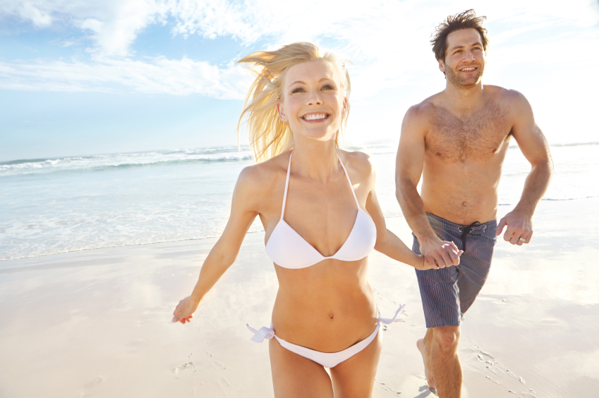 Shot of a young couple running on a beach